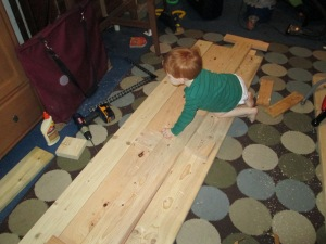 "Josh ""helps"" me measure and cut the side rails on his big brother's bed."
